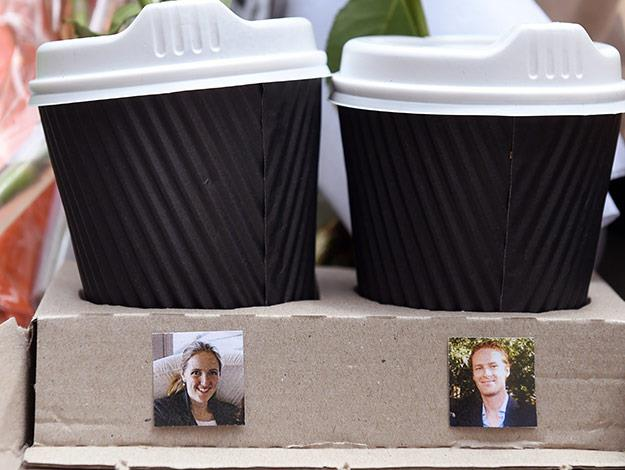 A cardboard tray with two coffee cups shows photos of Katrina Dawson (L) and Tori Johnson (R).