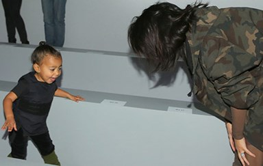 A rare look at Kim Kardashian playing with North West backstage at Kanye's show