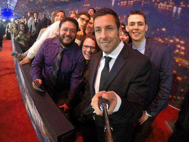 Adam Sandler takes a selfie with fans on the red carpet.