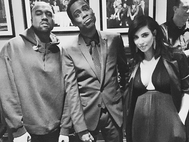 Kim Kardashian and Kanye West pose backstage with Chris Rock ahead of Kanye's musical performance on the show.