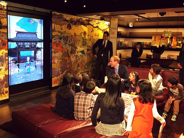 The Prince laughed along with Japanese children as a cartoon image of him appeared on a screen after he scanned in one of their drawings, during his visit to the British-designed bookshop Tsutaya.