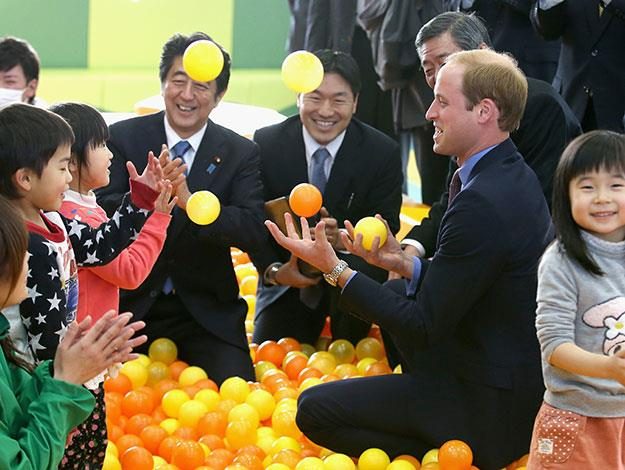 Clearly good with kids, Prince William gave them another laugh at Smile Kid's Park, showing off his juggling skills as he visited along with Prime Minister Shinzo Abe.