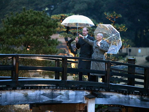 Walking over over a traditional Japanese bridge in on a tour of Hama Rikyu Gardens with Tokyo Governor Yoichi Masuzoe.