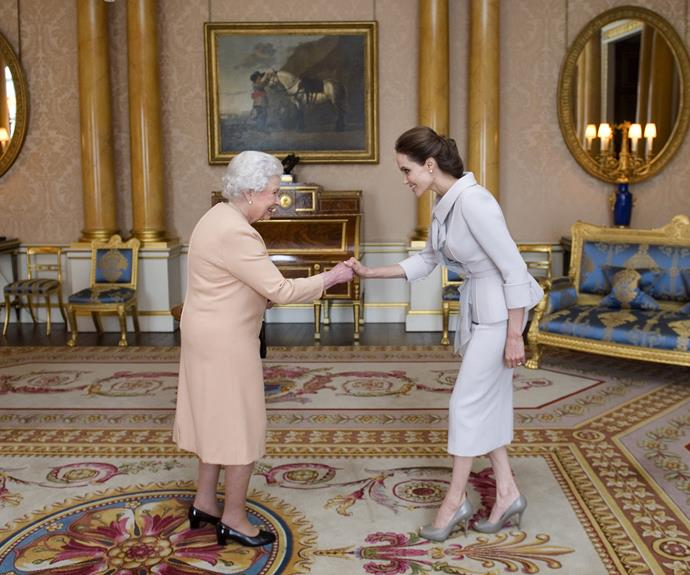 The Queen honours Angelina Jolie as an 'Honorary Dame' during a private audience in the 1844 Room and Buckingham Palace. Photo: WPA Pool via Getty