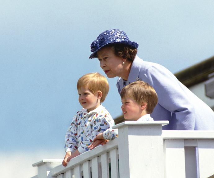 The Queen huddles close to her grandsons Prince William and Prince Harry in the Royal Box at Guards Polo Club in Windsor. Photo: Tim Graham/Getty