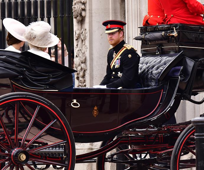 Prince Harry sits in a carriage alongside Catherine and Camilla.