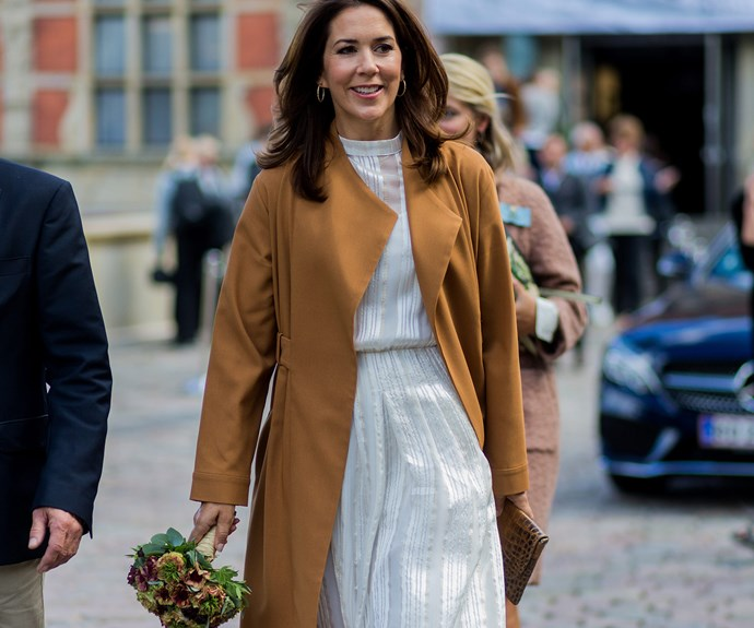The 45 year old in a camel coat and ivory dress.