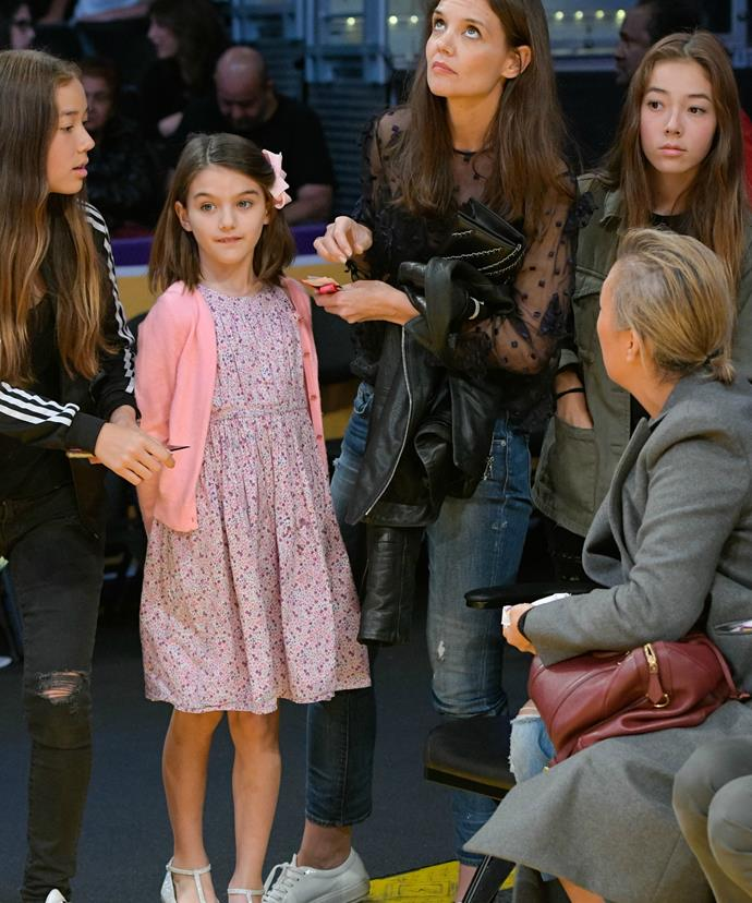 Suri was dressed in a pretty pink ensemble for the game, while Katie rocked jeans and sneakers.