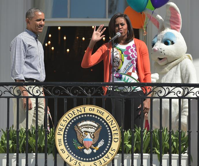 Michelle Obama speaking at the annual White House Easter Egg Roll, with her husband, Barack, standing beside her.