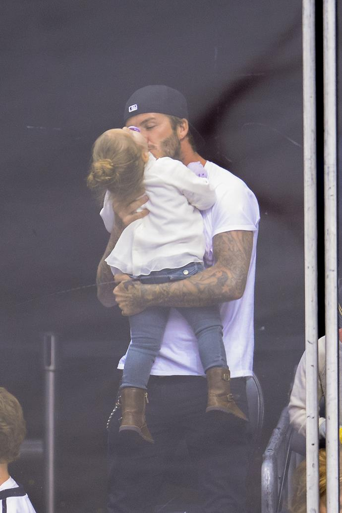 David plants a kiss on his daughter Harper at the Staples Center in LA.
