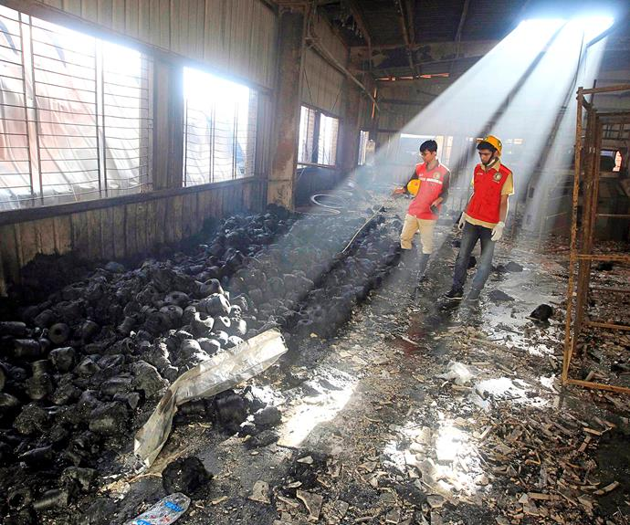 Rescue workers examine what remains of a factory after a fire. PHOTO: Nick Cubbin.