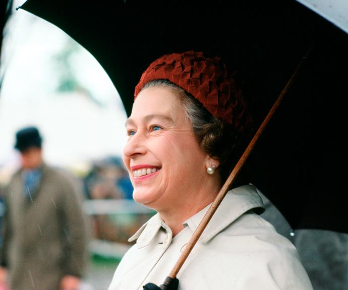 A smiling Queen Elizabeth in the rain.