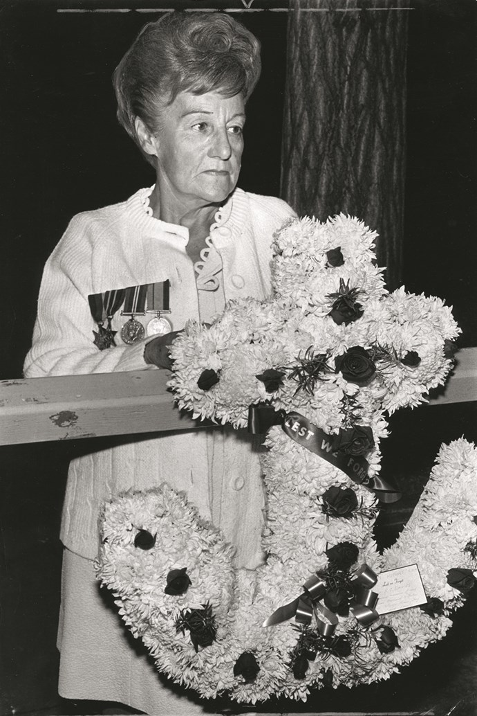 A woman wearing medals of honours hangs a wreath shaped as an anchor.