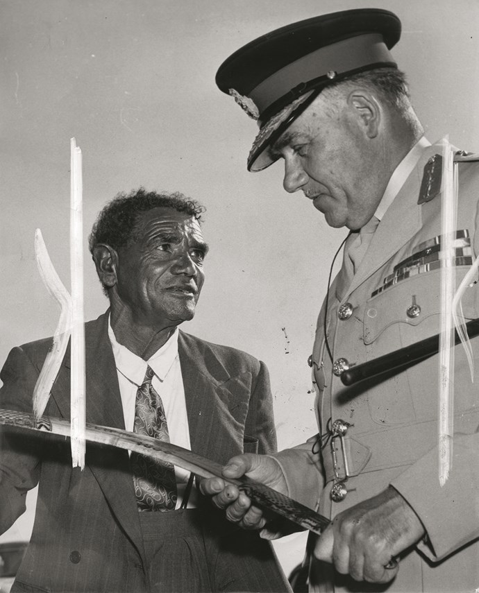 An aboriginal man gifts a traditional weapon, a boomerang, to an officer.