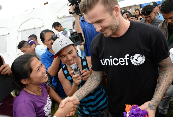 England football superstar David Beckham (R) greets survivors of devastating Typhoon Haiyan during a visit to a tent city in Tacloban city, Leyte province, central Philippines on February 13, 2014. Beckham visited the Philippines on February 13 to give comfort to survivors of the Asian country's deadliest ever typhoon -- although not everyone was sure of his identity. AFP PHOTO / TED ALJIBE (Photo credit should read TED ALJIBE/AFP/Getty Images)