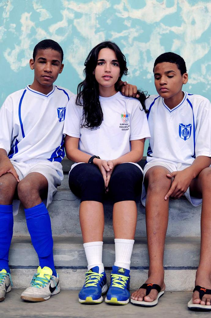 """Rhaiane Leitão de Andrade (center) coaches football to blind children and adults. She sits with two of her students Felipe Sabine (left) and Thiago Nascimento (right) at a national tournament in Belo Horizonte, Brazil. Working with the blind and vision impaired boys is no problem - they respect and learn from her, plus she's used to being the only girl around because she's grown up being involved in football. Out of the nine teams for blind players in Brazil, she is the only woman among all the coaches and players. She says she would like to start a girls team, but that, """"It's difficult to find a woman who plays a man's sport - it's even more difficult to find a blind woman who plays."""" **Picture by Isabella Melody Moore via [itswhatartis](http://itswhatartis.com/)**"""