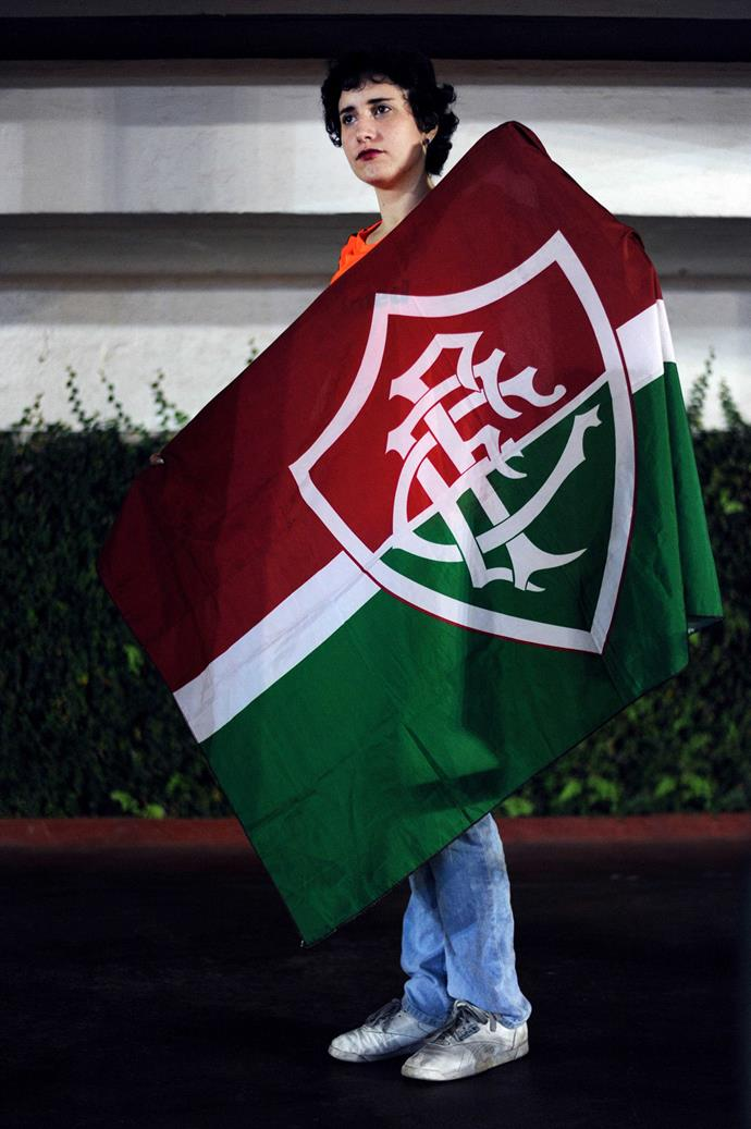 Danielle Lott, with the flag of her soccer team, Fluminense. Danielle and her female friends are among the most active supporters at her team's games, but they face discrimination and violence for being female fans from opposing supporters. Ever since she and other female fans were caught in the middle of a fight leaving a rival team's stadium, she has taken up jiu-jitsu and other martial arts classes to protect herself. **Picture by Isabella Melody Moore via [itswhatartis](http://itswhatartis.com/)**