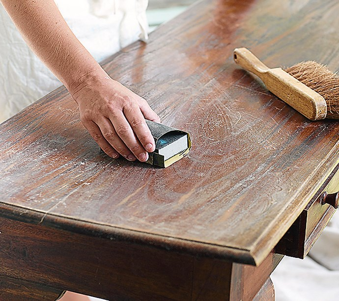 **STEP 3** Use medium grit sand paper to rough up the surface of the table. It isn't necessary to remove all the old finish; you're just trying to create a surface that paint will adhere to.