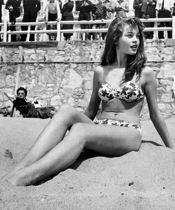 French actress Brigitte Bardot sitting on the beach during the Cannes Film Festival, 1953.