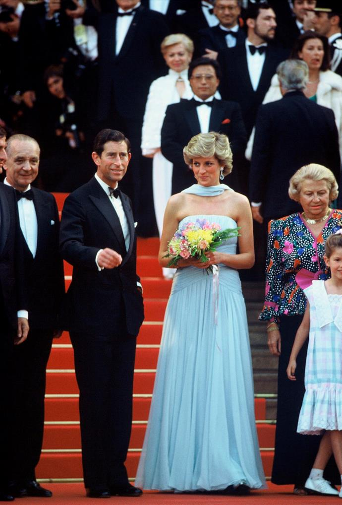 Princess Diana, Princess of Wales, wearing a pale blue chiffon dress and matching stole by Catherine Walker, and Prince Charles, Prince of Wales attend Cannes film festival on May 15, 1987.