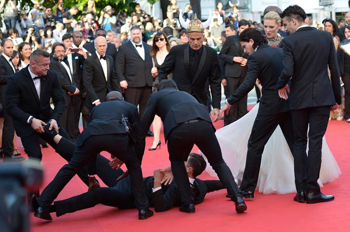Ukrainian journalist Vitalii Sediuk is blocked by minders as he tries to slip under US actress America Ferrera's dress as she arrives for the screening of the animated film *How to train your Dragon 2* at the 67th Cannes Film Festival in Cannes, 2014.