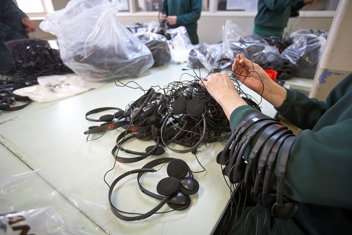 A worker sorts through airline headsets at Silverwater Women's Correctional Centre. She'll be paid 40c per bag of 50 completed headsets. PHOTO: Nick Cubbin.