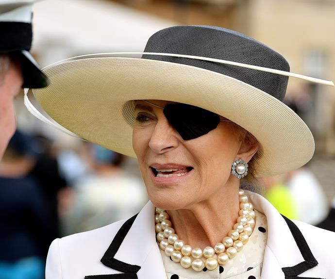 Her hat sported a single white feather stem, and she teamed it with some seriously big pearls.