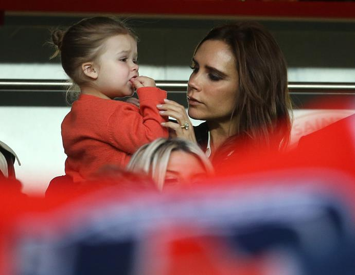 Victoria Beckham and her daughter Harper Seven in the stands at one of David's games in 2013.