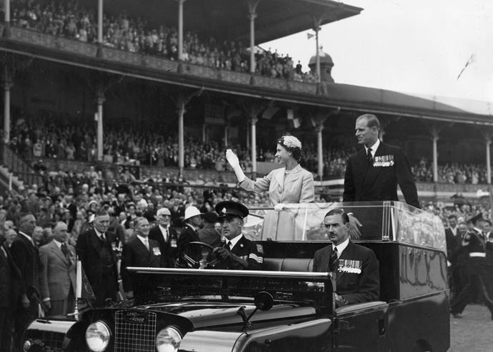 Elizabeth and Philip wave to crowds as they are driven around the Melbourne Cricket Ground.