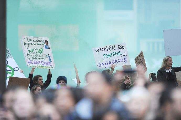 Carrying signs that said 'Dead women can't vote' and 'Cuts kill', the protesters chanted 'We are suffragettes'.