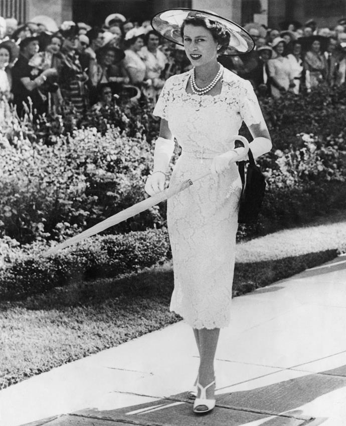 HARDY AMIES' WHITE LACE WOW The Queen wore this stunning tailored white lace dress by one of her favourite couturiers, Hardy Amies, with matching gloves, tightly furled umbrella and stylish black-crinoline brimmed hat trimmed with red and green ostrich feathers in 1954 at a garden party at Government House in Sydney. She teamed the outfit with white peep-toe sandals and pearls. It was an immediate fashion sensation and has been referenced ever since as an example of Her Majesty's style cred.