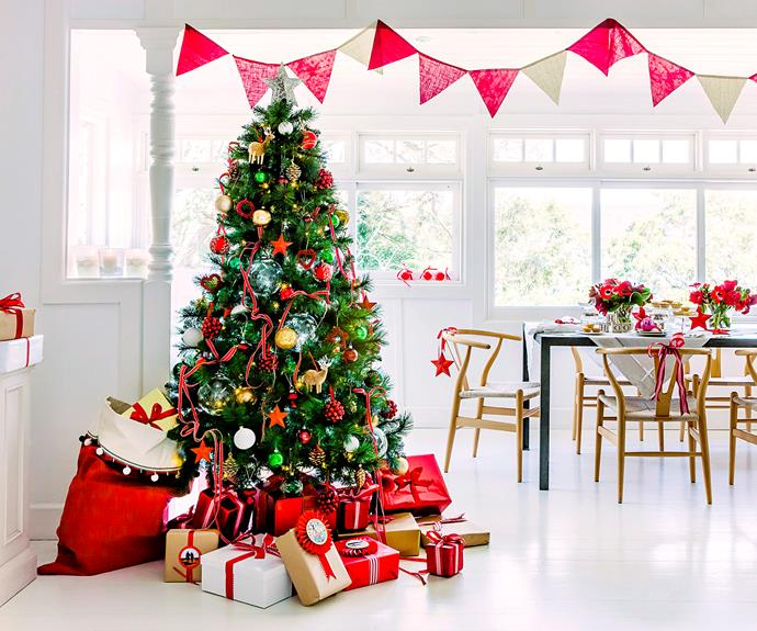 The traditional Christmas tree is busily adorned with many decorations, including twinkling lights and glass baubles, and topped with the ubiquitous angel or star.