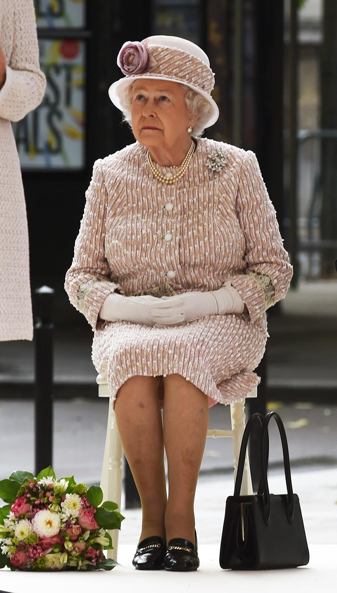 The Queen's handbag contains good luck charms from her children, including miniature dogs and horses, and family photos. Another reason it never leaves her side is because it's used as a signalling device. Placed on the table it means she wishes to leave in five minutes. Switched from arm to arm means she must move on and talk to someone else.