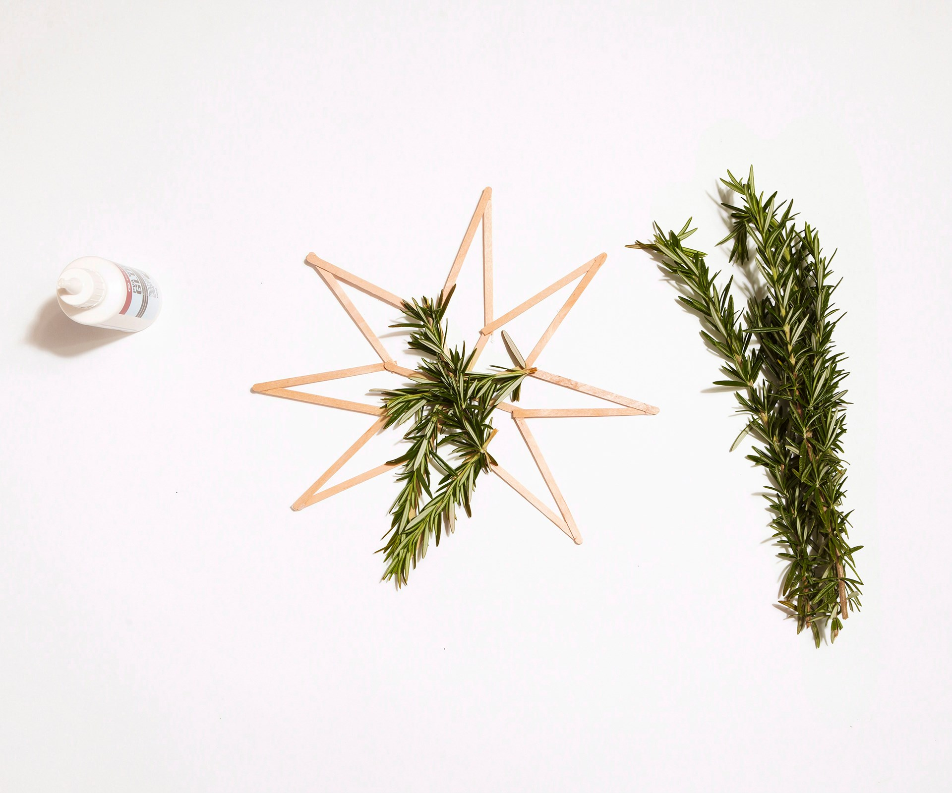 Cut your greenery into pieces the same lengths as the sections of the wooden strips. Hot glue the cut greenery to the sticks. Leave to dry. Tie coloured ribbon onto dry stars and hang.