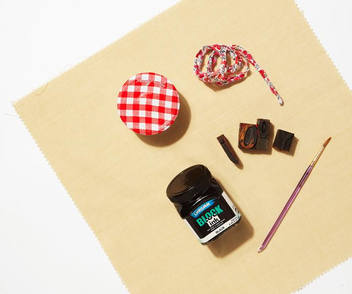 "Lay out your jar or gift item on the linen and experiment with wrapping it up. Cut fabric around the gift in a square shape, allowing yourself enough fabric for long ""ears"" at the top (to achieve raw edges, simply make a small cut with your scissors and rip fabric in a straight line before cutting off any loose threads, or use pinking shears for an un-frayed finish)."