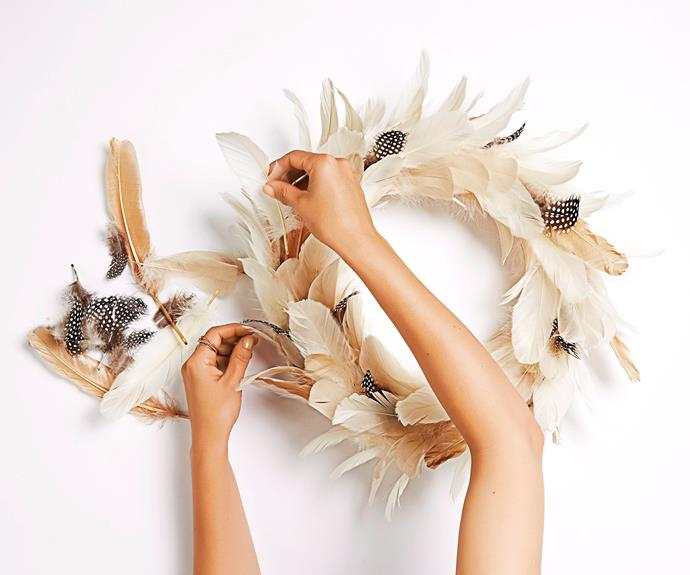 Using smaller feathers, carefully fill in any gaps that may have appeared between the larger feathers.