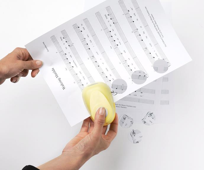 Using a circle punch, cut out small circles from the sheet music. Continue cutting these out until you have a large amount, depending on how long you want your garland to be.