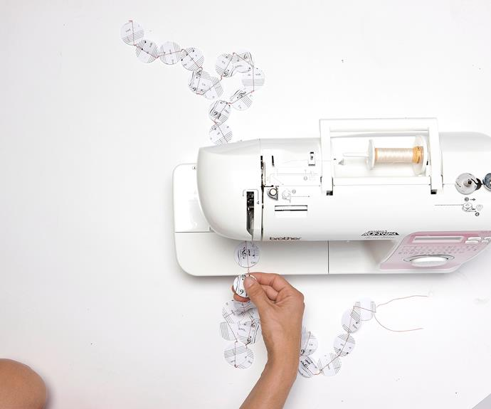 Place two circles on top of one another and, using a sewing machine threaded with red cotton, sew together your punched circles in a chain pattern, one after another. It will be much easier to control the paper if you set your sewing machine to a slow speed.