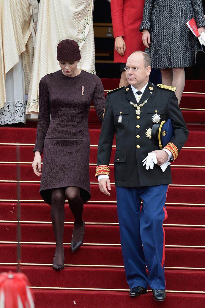 Princess Charlene looked very respectable in a plum outfit by Akris. Prince Albert donned in military regalia.