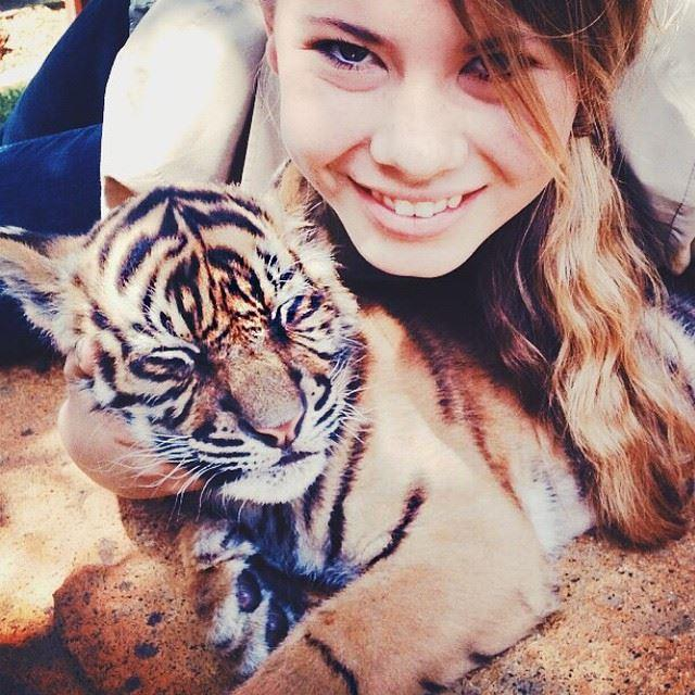 With a tiger cub, via her Instagram.