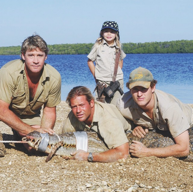 """Here's a #flashback to a 6 year old Bindi helping Dad and the croc boys secure a beautiful and giant salt water crocodile. In Far North Queensland, carrying my Dad's knife belt, these were the best days. Please note two things about me - I was so little, the belt had no hope of fitting..so I had to carry it on my shoulder! Also, my epic star hat, because you have to have style when you're catching crocs!"""