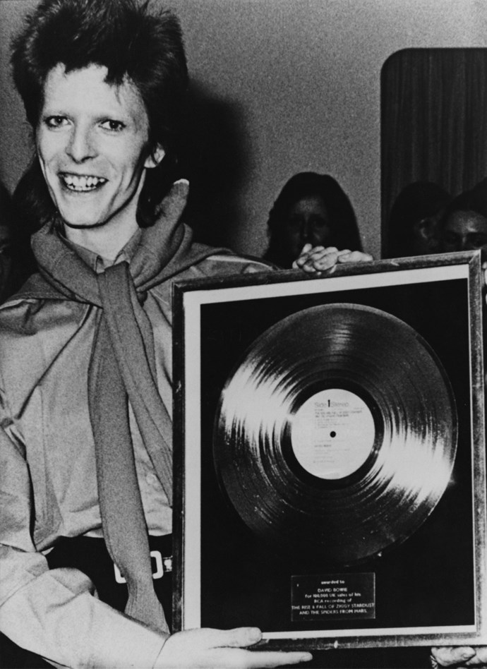 Bowie in 1972 with a gold record celebrating selling 10o,oo of his album *The Rise and Fall of Ziggy Stardust and the Spiders from Mars.*