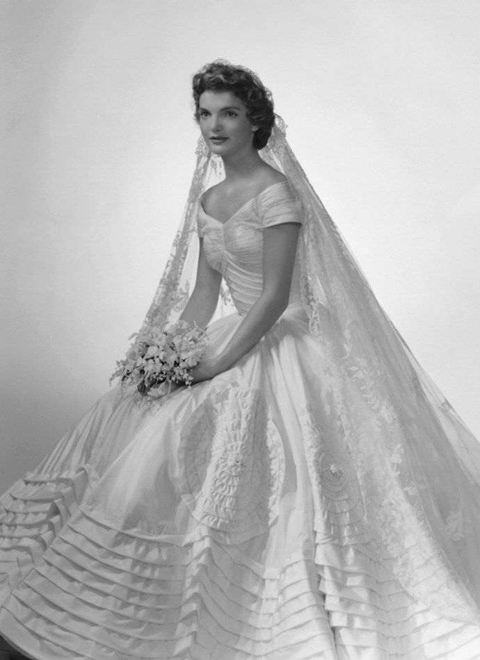 Bridal portrait of Jacqueline Lee Bouvier (1929 - 1994) shows her in an Anne Lowe-designed wedding dress, a bouquet of flowers in her hands, New York, New York, 1953. (Photo by Bachrach/Getty Images)