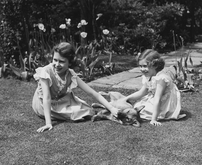 June 1936: Queen Elizabeth II (as Princess Elizabeth) and her younger sister Princess Margaret (1930 - 2002) sitting on the grass in the grounds of the Royal Lodge, Windsor, stroking a corgi.