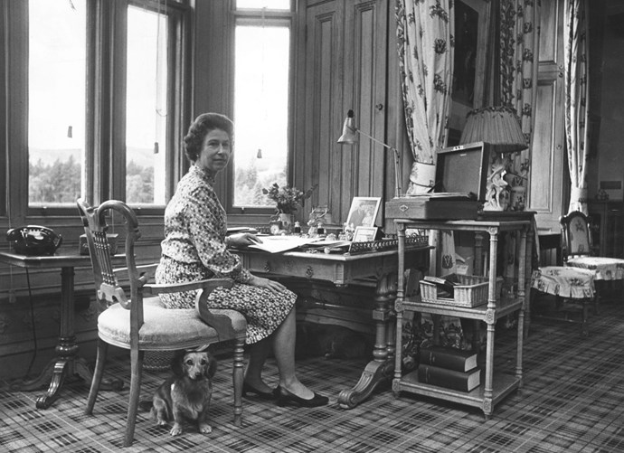 October 1972: Queen Elizabeth II sitting in her study at Balmoral Castle with a corgi at her feet.