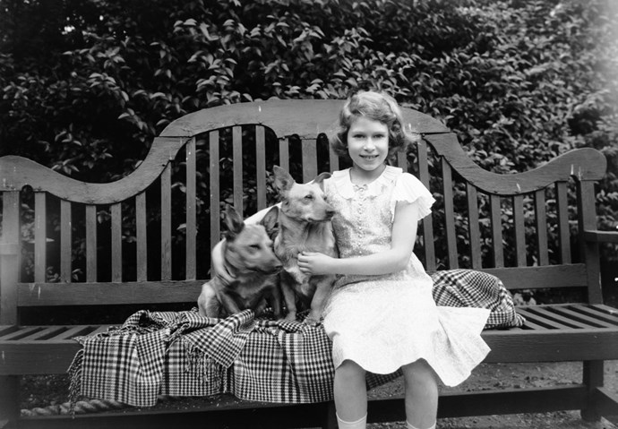 July 1936: Princess Elizabeth sitting on a garden seat with two corgi dogs at her home.