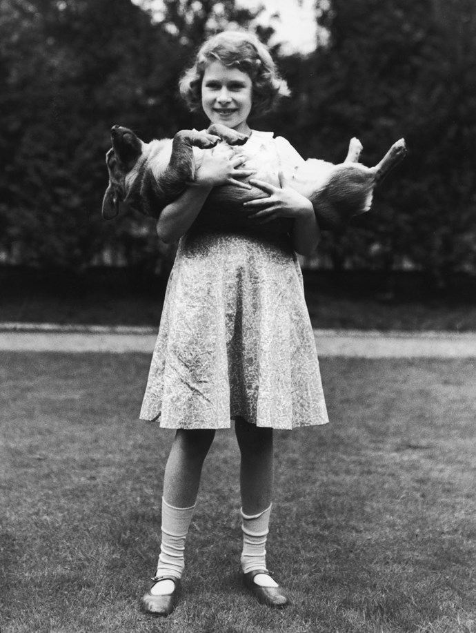 A young Princess Elizabeth holding a corgi dog.