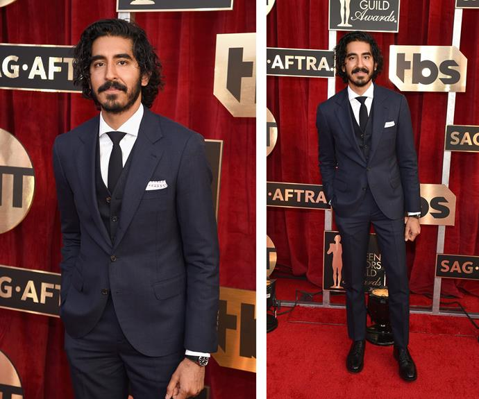 Supporting Actor nominee Dev Patel looks sharp in his navy, three-piece suit.