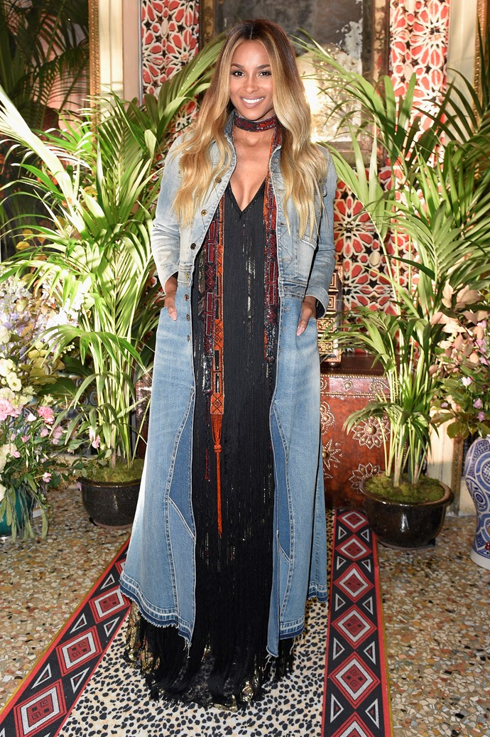 Ciara looks next-level fresh at the Roberto Cavallo FROW in her denim overcoat and fringed maxi.