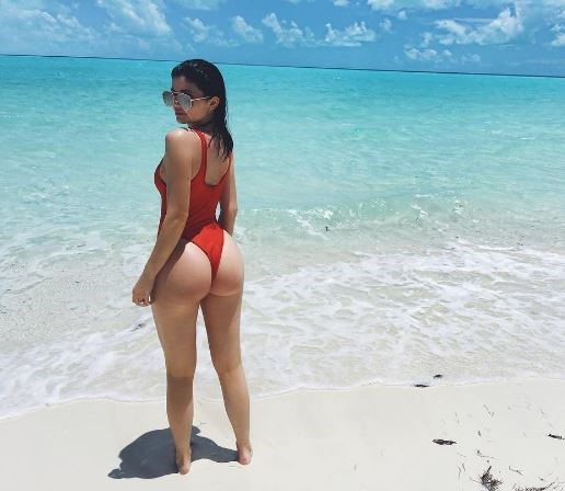 Kylie Jenner took a page out of the *Baywatch* book in her latest Insta throwback, rocking an uber high-cut red swimsuit even C.J. Parker would approve of. Ky-lizzle obvs looks INCRED ('cause Kylie), with one helluva toned booty and a pair of aviators which practically ooze IDGAF attitude.